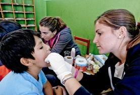 A Dentistry Elective volunteer inspects a patient on a placement in Peru