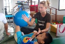 An intern doing her Physiotherapy Elective in a developing country works on mobility exercises with a disabled child.