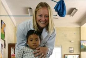 A Medicine volunteer smiles with a child on a placement in Nepal