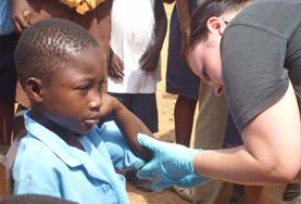 A Nursing volunteer checks a child's heart rate as part of her Medical internship abroad.