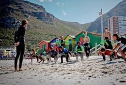 A volunteer works with local children on their surfing technique during a lesson in South Africa.